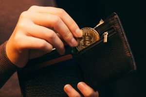 woman putting bitcoin in wallet